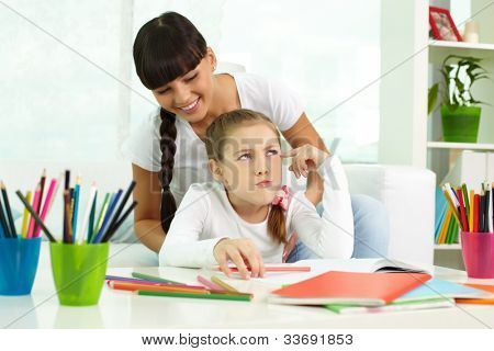 Portrait of cute girl thinking while drawing with colorful pencils with her mother near by