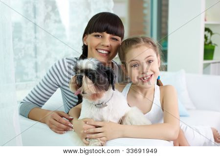 Portrait of happy girl and her mother holding pet and looking at camera with smiles