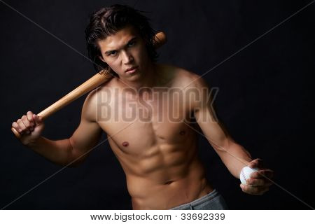 Image of shirtless man with baseball bat looking at camera
