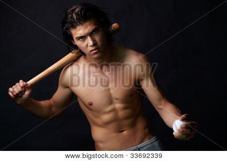 Image of shirtless man with baseball bat looking at camera