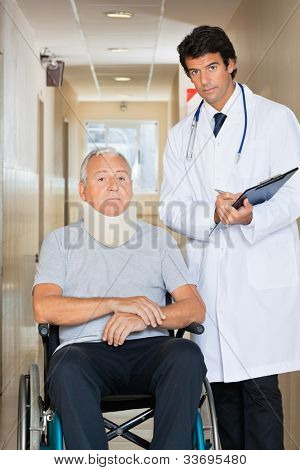 Young doctor writing on clipboard by senior man sitting on wheel chair with neck brace