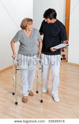 Full length of a trainer holding clipboard and looking at senior woman using walker