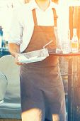 Hand Of Waiter Is Holding A Tray With Dirty Dishes And Empty Glasses And Bottles. Waiter Cleaning Th poster
