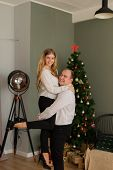Happy Husband And Wife At The Christmas Tree At Home. Husband Holds His Wife In His Arms. poster