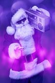 Cool DJ Santa Claus in sunglasses holds tape recorder on a festive background with lights. Christmas poster