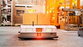 warehouse robot car carries cardboard box assembly in factory poster