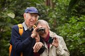 foto of senior-citizen  - Senior man helps wife look through binoculars in forest - JPG