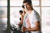 Happy Fit People Running On Treadmill At Fitness Gym Club poster