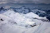 Mountains Around Top Of Shilthorn, Switzerland Covered By Snow With Overcast Sky In Winter. poster