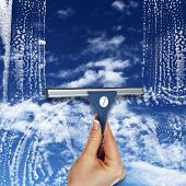 stock photo of cleaning service  - Hand cleaning window with blue sky and white clouds - JPG