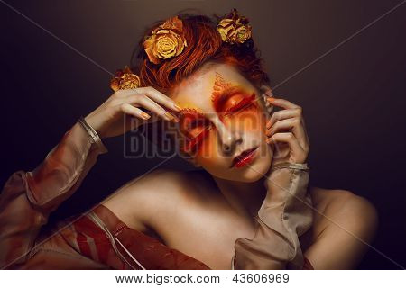 Bodyart. Imagination. Artistic Woman With Red - Gold Makeup And Flowers. Coloring