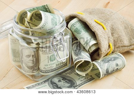 Dollar Banknote  In  Glass Jar And Bag Of Money