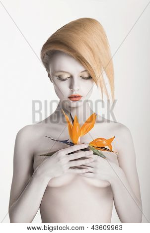 Bodypainting. Enigmatic Gorgeous Woman With Strelitzia Flower In Hands. Painted Skin