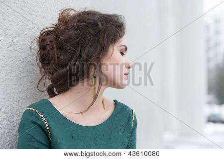 Romantic Caucasian Woman In Green Dress Over White Wall Outside. Solitude