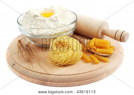 Bakery Ingredient. Flour With Raw Eggs For Making Dough On The Wooden Board.