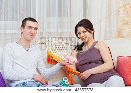 pregnant woman with the husband look clothes for the child