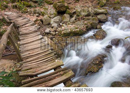Silky Smooth Water Under A Wooden Bridge