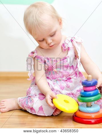 Little Baby Girl Playing With Colorful Child Pyramid