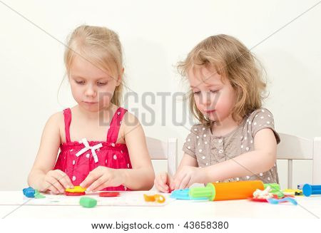 Dos niñas escultura utilizando plastilina
