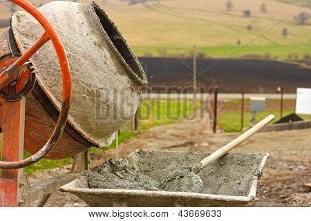 Close-up Of Concrete Mixer And Wheelbarrow