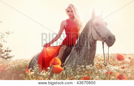 Gorgeous Blonde Woman Riding A Horse In Fashionable Red Dress.