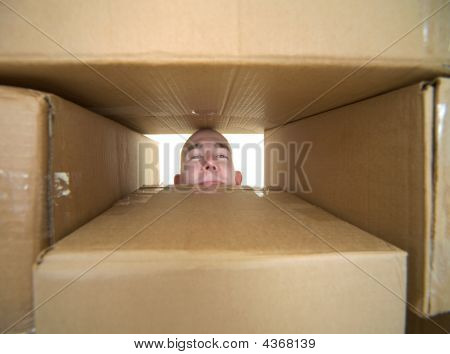 Face Looking Trough Window In Pile Cardboard Boxes