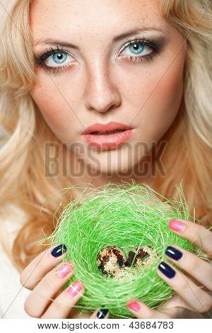 mujer que sostiene el nido con codornices huevos