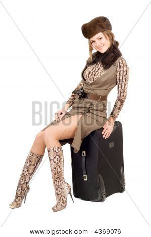 Young Lady Sits On A Suitcase. Isolated
