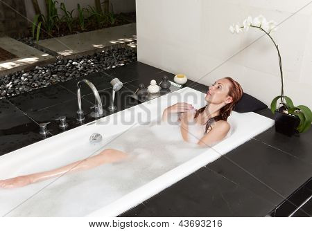 woman lays in soapsuds in bathing full water