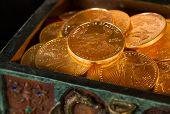 stock photo of treasury  - Stacks of gold eagle one troy ounce golden coins from US Treasury mint in old carved pirate treasure chest - JPG