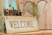 stock photo of timber  - Rustic wooden WELCOME sign standing on a wooden shelf in front of a wood panel with a cut out heart offering a warm country welcome - JPG
