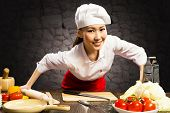 stock photo of over counter  - Asian woman cook leaned over the table and looking into the camera - JPG
