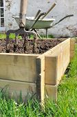 picture of planters  - spade in a wooden planter for vegetable garden - JPG
