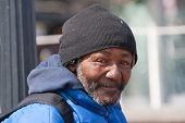 stock photo of hobo  - Happy homeless african american man outdoors during the day - JPG