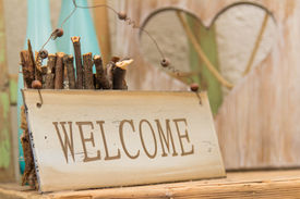 image of politeness  - Rustic wooden WELCOME sign standing on a wooden shelf in front of a wood panel with a cut out heart offering a warm country welcome - JPG