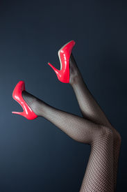 picture of fishnet stockings  - A pair of shapely female legs in fishnet stockings with shiny red high heeled shoes on a dark background - JPG