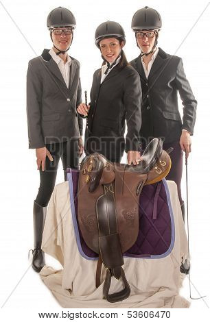 three beautiful young people with horses outfit and a saddle