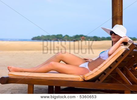 Brunette In White Hat On Chaise Longue