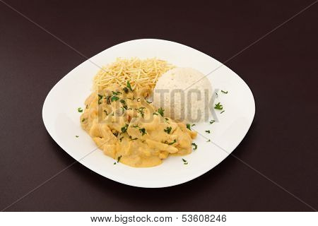 Chicken stroganoff dish with shoestring potato and rice on brown leather background.