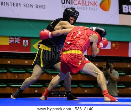 KUALA LUMPUR - NOV 03: Iraq's Husam Mohammed (black) trades pinches with Russia's Magomedov Ali (red) in the Sanda event, 12th World Wushu Championship on November 03, 2013 in Kuala Lumpur, Malaysia.