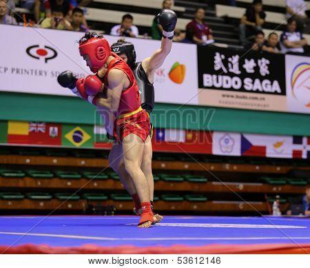 KUALA LUMPUR - NOV 03: Malaysia's Tan Jia Guan in red tries to take down Sweden's Johan Lindqvist in the Sanda event, 12th World Wushu Championship on November 03, 2013 in Kuala Lumpur, Malaysia.