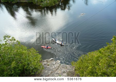 Kayaker And Canoeists Viewed From Cliff Edge