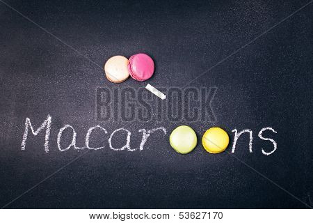 Colourful French macaroons over a chalkboard. The word MACAROONS has been written in chalk and the OO has been replaced by macaroons.