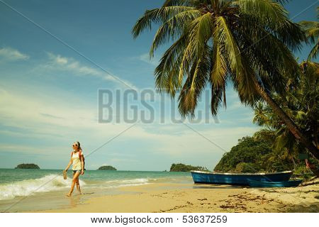 Young lady tourist walking along tropical sandy beach with palm trees. Koh Chang, Thailand
