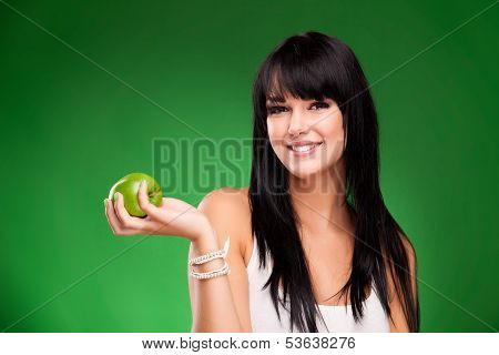 Beautiful Brunette Woman With Green Apple On Green Background