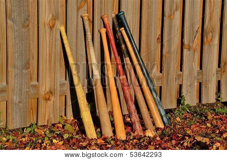 Baseball bats lean on a  fence