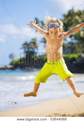 Young happy boy having fun on tropical beach, jumping into the air