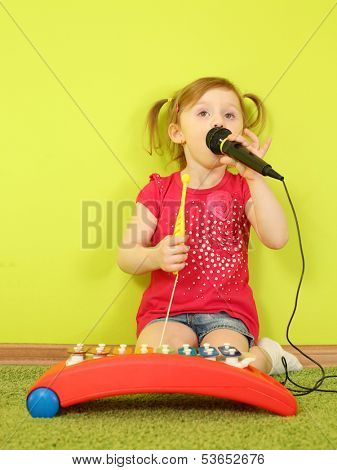 Little girl singing into a microphone and playing on metallophone