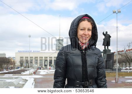 A smiling woman is standing against the Finlyandskiy railway station, St. Petersburg, Russia