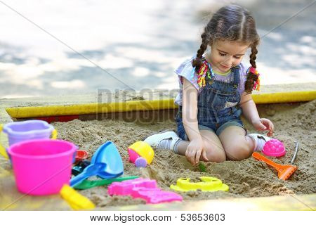 Little girl sitting in the sandbox and playing with molds on the playground